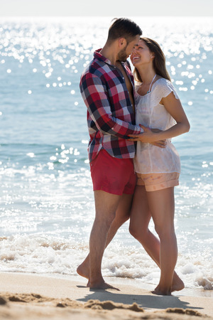 romantic date: Happy young couple having romantic date on sandy beach at sunny day Stock Photo