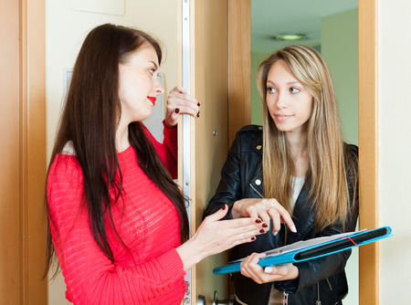 census: young female employee polling among people at home  door. Focus on blonde Stock Photo