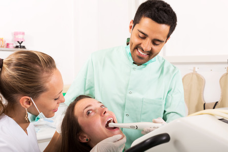 oral cavity: Cheerful male dentist examines the oral cavity on computer equipment Stock Photo