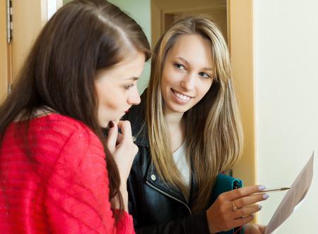 encuestando: joven empleada de votación entre las personas en la puerta. Centrarse en rubia