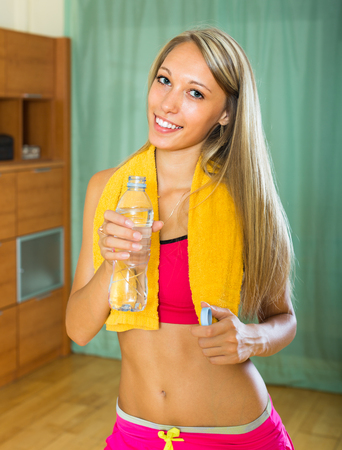 house trained: Happy smiling sporty girl with bottle of water after exercising indoor