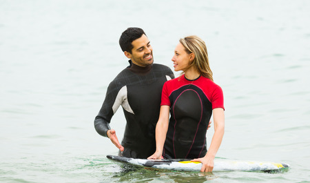 waist deep: Happy smiling active couple swimming in wetsuits with surf board