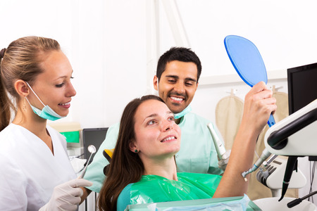 trained nurse: Woman patient checks the result of the work of the dentist. Focus on the patient Stock Photo