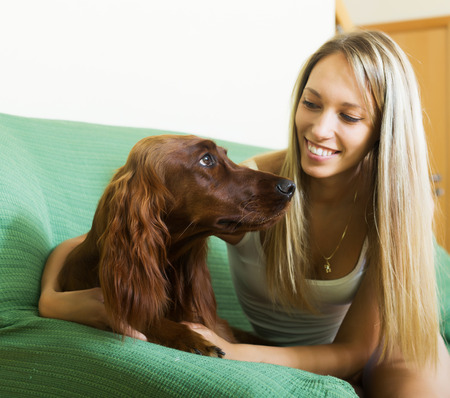 setter: Happy girl sitting with red Irish setter