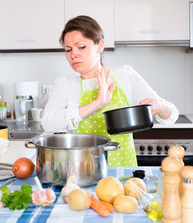 smell: Caucasian woman in green apron in kitchen opened a bad smelling pan Stock Photo