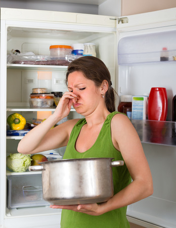 frowy: Girl holding pan with foul food near refrigerator at home kitchen