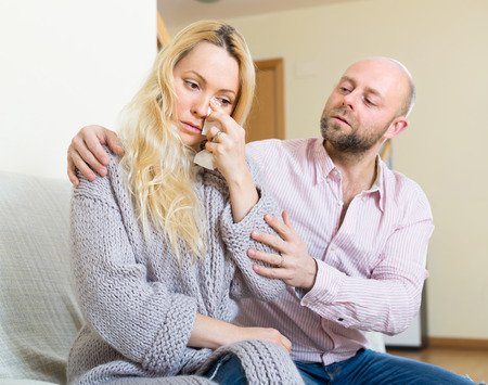 argument from love: Man asking for forgiveness from crying woman after quarrel at home. Focus on girl Stock Photo