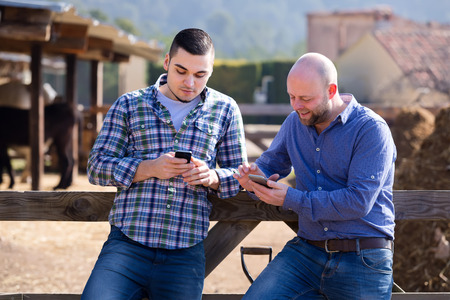 Two ranchers having a break after hard work on a farm. They are leaning on a wooden fence and playing on their smartphones