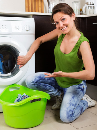 18 20: Home laundry. Smiling brunette woman loading clothes into washing machine