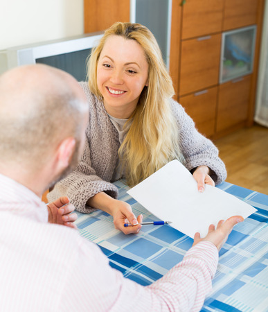 hypothec: Joyful smiling couple discussing details of marriage settlement indoors Stock Photo