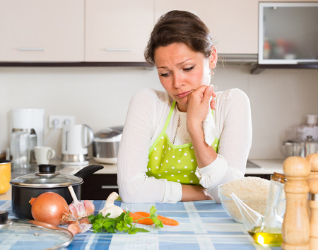 Young tired woman in apron cooking rice in the kitchen at home