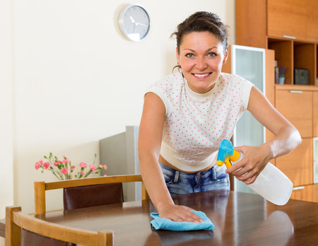 atomizer: Young smiling woman polishing furniture with atomizer and rag