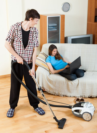 disparity: Clean up man, while wife lying with laptop on the sofa Stock Photo