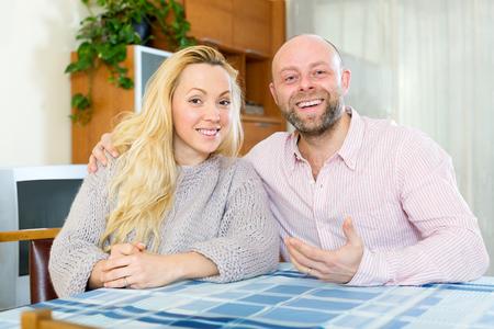Sonriente pareja de enamorados en casa en la sala de estar