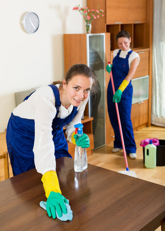 service occupation: Professional happy european cleaners cleaning in room