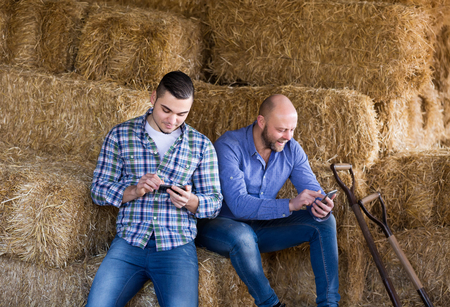 hayloft: Portrait of two positive smiling male farmers with phones at hayloft. Selective focus