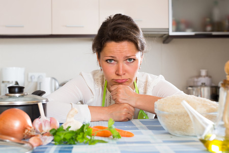25 35: Sad tired woman cooking rice in the kitchen