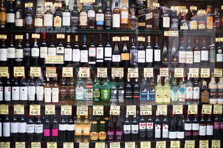 spirituous beverages: BARCELONA, SPAIN - OCTOBER 27, 2015: View at glass display of ordinary liquor store with alcoholic beverages in bottles