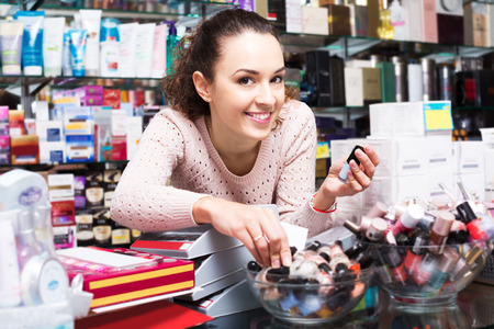 30 35: Portrait of young smiling brunette selecting nail polish in beauty store