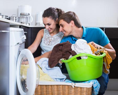 lavando ropa: Marido ayudando feliz ama de casa española de usar la máquina de lavar en el interior Foto de archivo