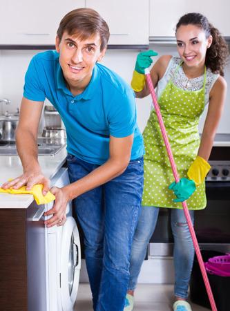 servicio domestico: c�nyuges j�venes haciendo las tareas del hogar regular y pulido en la cocina dom�stica Foto de archivo