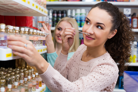 eau de perfume: Portrait of young positive female customers shopping in beauty store