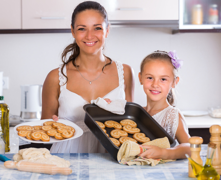 25 35: Portrait of happy housewife and daughter with homemade pastry Stock Photo