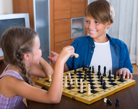 ni�os inteligentes: Portrait of happy children at chess board together Foto de archivo