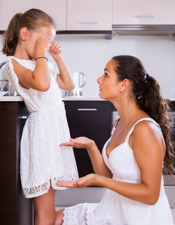 shaming: Crisis of motherhood: sad young woman preaching daughter Stock Photo