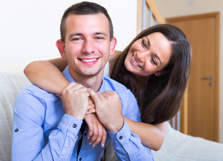 limp: Happy young spouses posing together in living room. Focus on guy