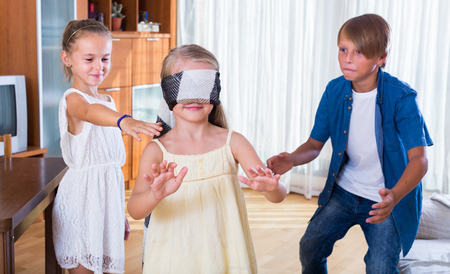 romp: Blindfolded child catching other players in Kagome at home