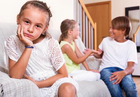 morose: Upset sad little girl is jealous sister of stepbrother indoors Stock Photo