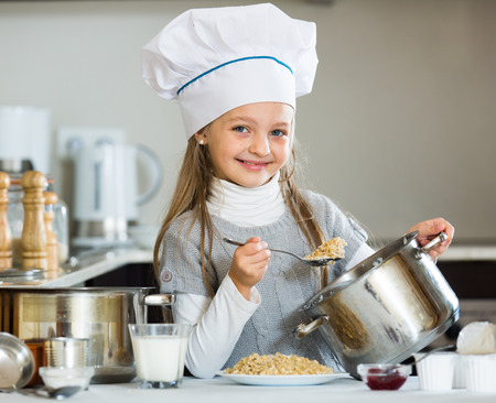 kasha: Small girl cooking oatmeal kasha in home kitchen and smiling Stock Photo
