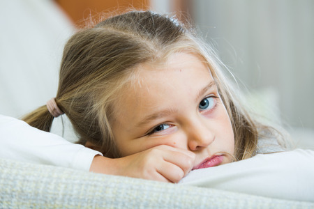 tedious: Frustrated little girl with ponytailes bored at home