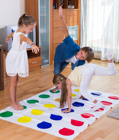 twister: Two cheerful cute little girls and teenage boy playing twister at home