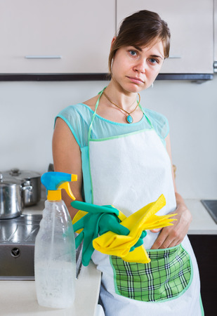 reluctance: Tired young woman in rubber gloves posing at the kitchen Stock Photo