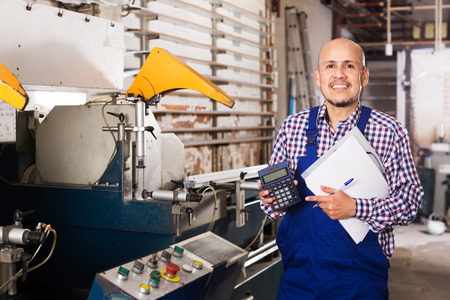 coverall: Positive male in coverall working on lathe machine at factory Stock Photo