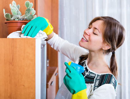cleaning up: Beautiful young woman doing regular clean-up and smiling indoors Stock Photo