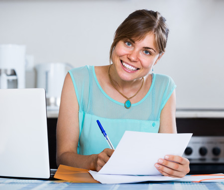 householder: Happy american adult girl applying for bank loan at home