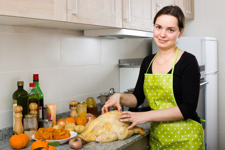 capon: Portrait of brunette girl in apron preparing capon at home kitchen Stock Photo