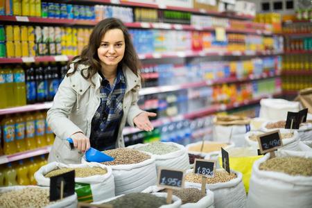groats: Ordinary female customer buying groats in supermarket Stock Photo