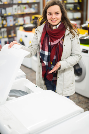 30 35: Positive young brunette choosing washing machine in hypermarket and smiling