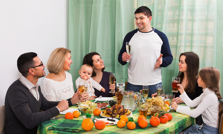 granny and grandad: Cheerful  multigenerational family sitting at holiday table, toasting and smiling Stock Photo