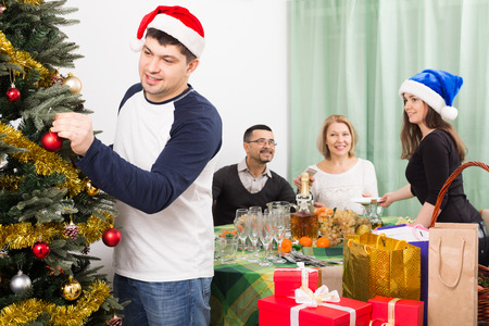 30 35 years: Mature parents with adult kids preparing for Christmas celebration indoors