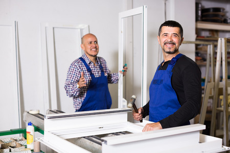 toolroom: Two professional workers in coveralls toiling with PVC window and door profiles at workshop