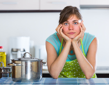 unwillingness: Portrait of tired young housewife at home kitchen