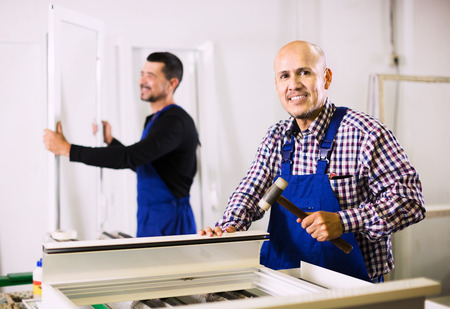 coverall: Two positive men in coverall working in PVC shop and smiling