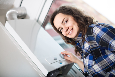 central european: positive american adult girl in shirt near boiler control panel