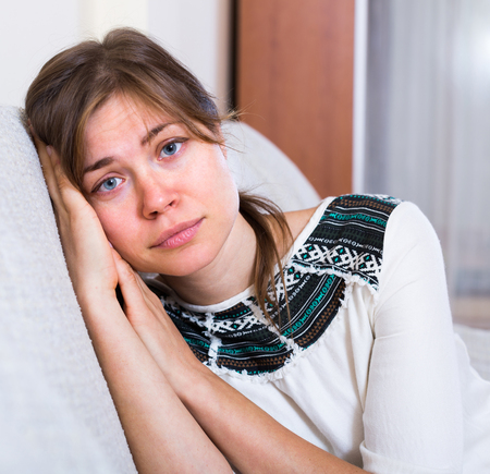 miserable: Portrait of miserable young woman sitting on sofa at home