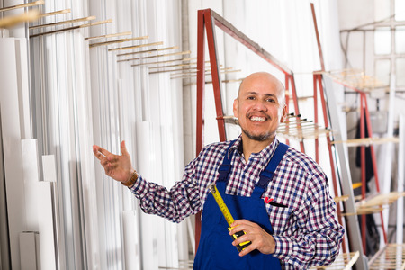 45 50: Male middle age worker working in PVC shop and smiling